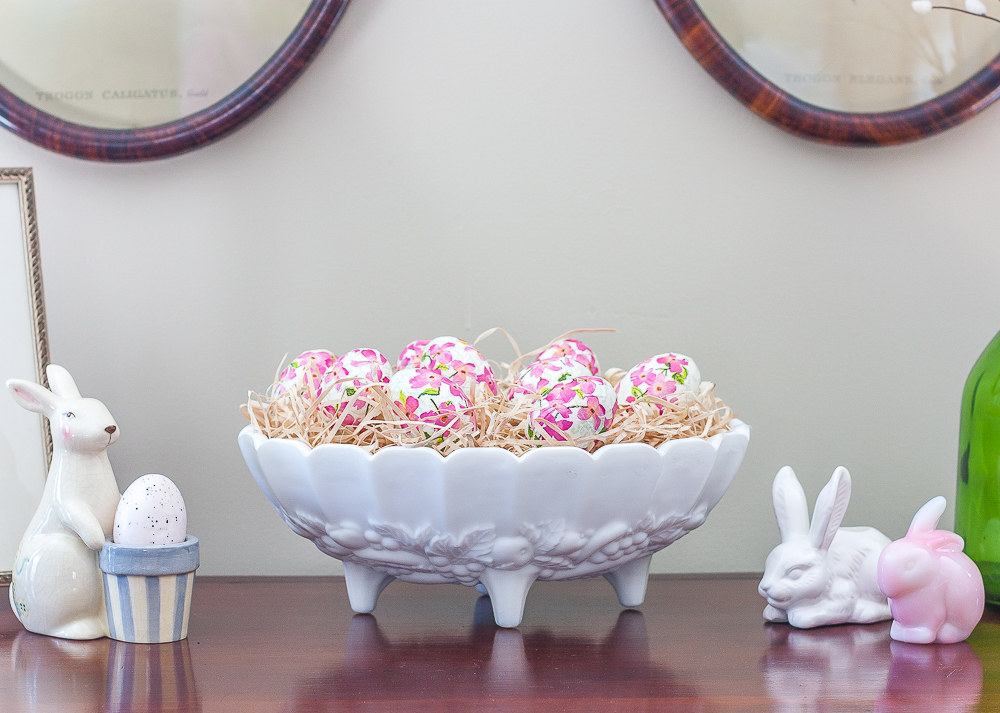 Decoupaged Easter eggs displayed in a milk glass fruit bowl with bunnies displayed on either side