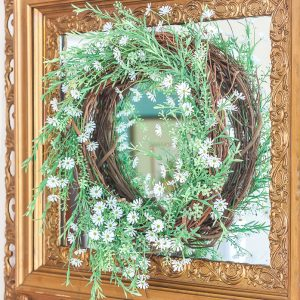 Spring wreath with greenery and tiny daisies hanging on an antique gold mirror