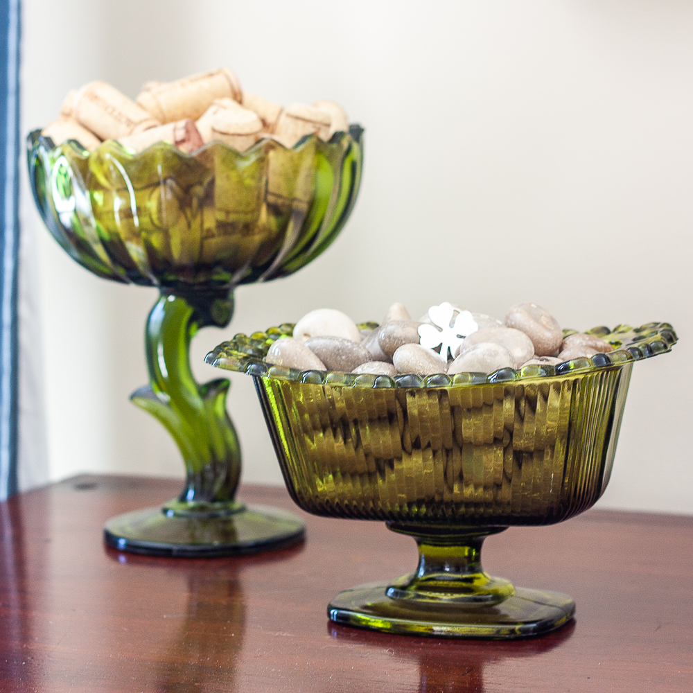 Green glass candy dishes filled with wine corks and polished stones