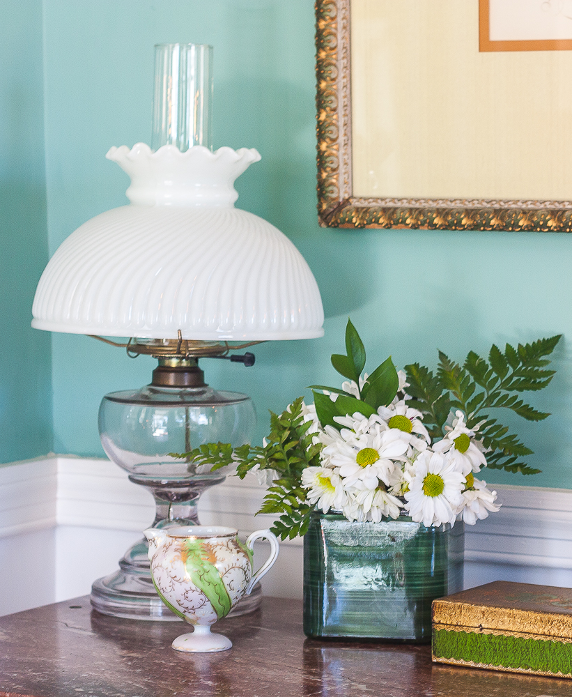 Antique lamp, antique green and gold pitcher, flower arrangement with daisies and ferns
