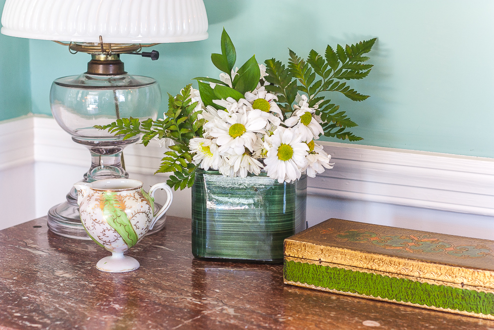 Antique lamp, antique green and gold pitcher, flower arrangement with daisies and ferns, and a vintage green and gold box