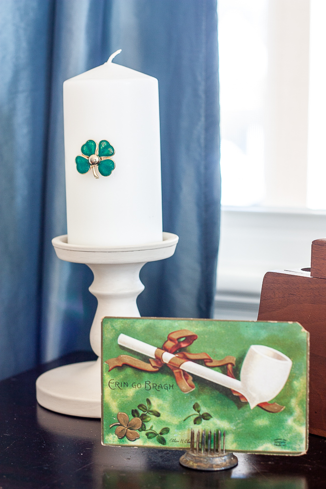 Antique St. Patrick's Day postcard and a candle on a candle holder with a green clover pin glued to it.