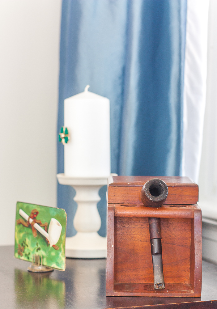Antique St. Patrick's Day postcard, pipe and tobacco box, candle on a candle holder with a green clover pin glued to it.