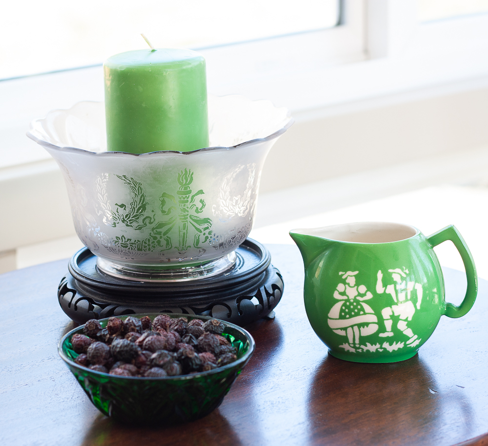 Czech green pitcher, antique green glass bowl, shade from an oil lantern decorated with a candle