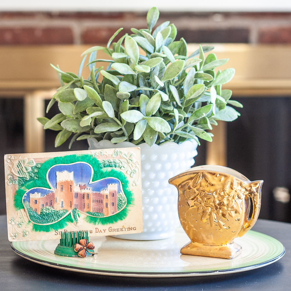 St. Patrick's Day vignette with a vintage postcard, gold pitcher, and a plant in a milk glass vase.
