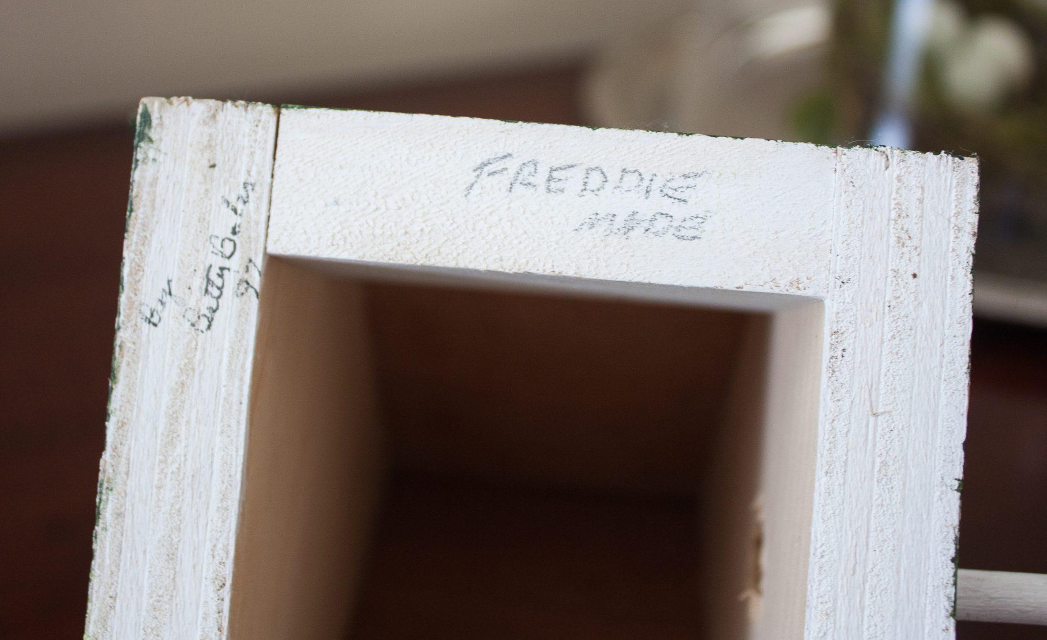Writing on the bottom of a handmade birdhouse