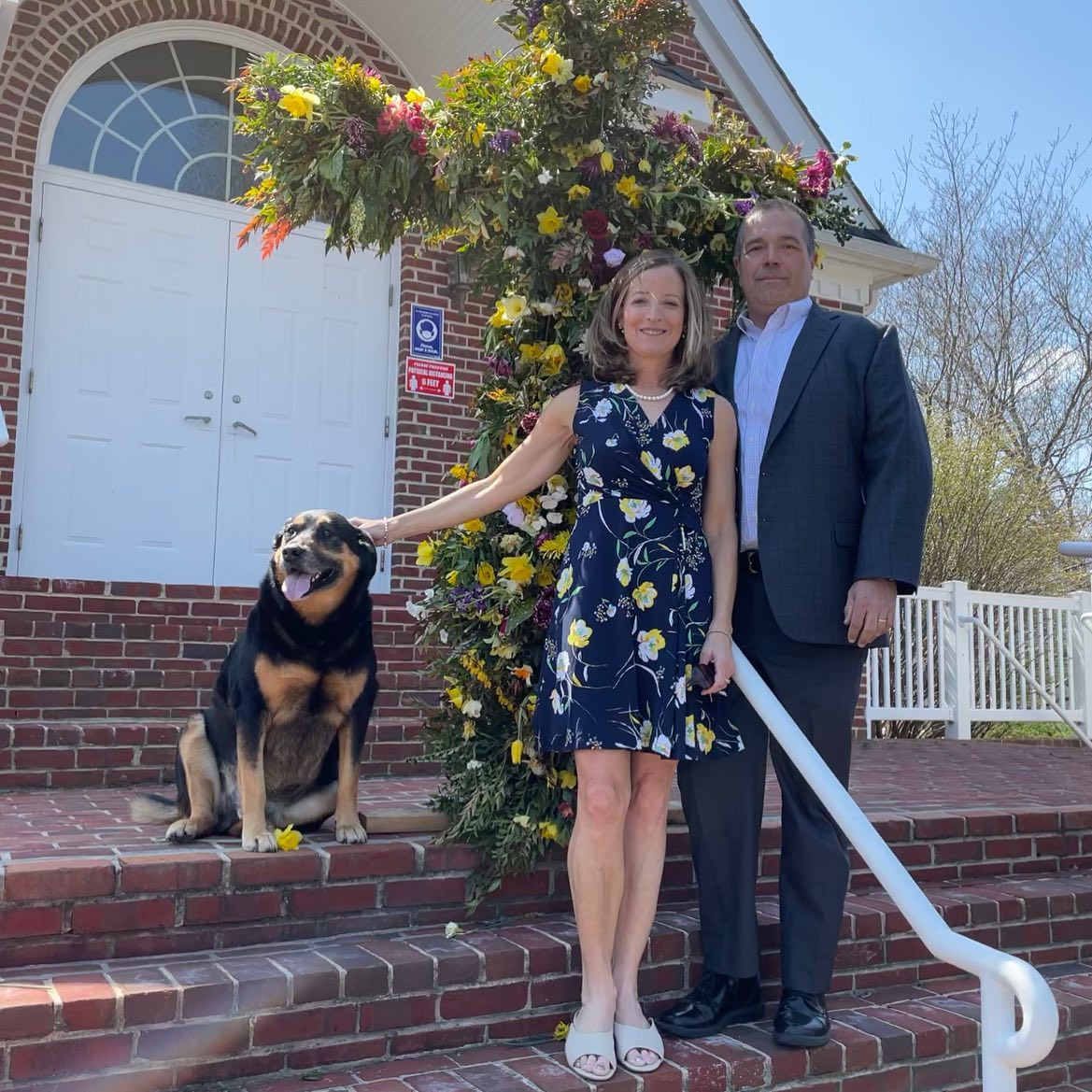 Couple and dog in front of a cross decorated with flowers on Easter Sunday