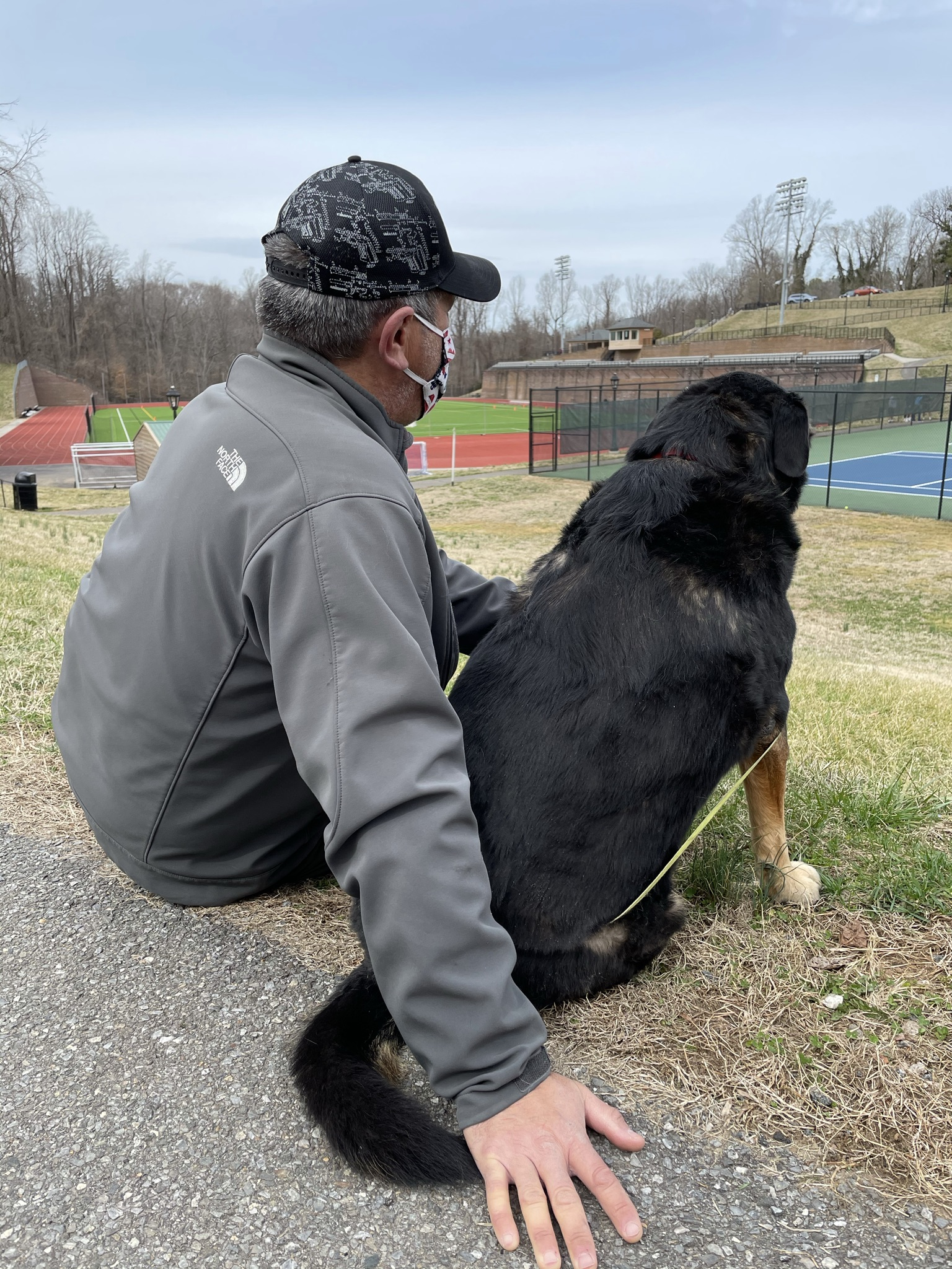 Man and dog watching tennis at Randolph College in Lynchburg, VA