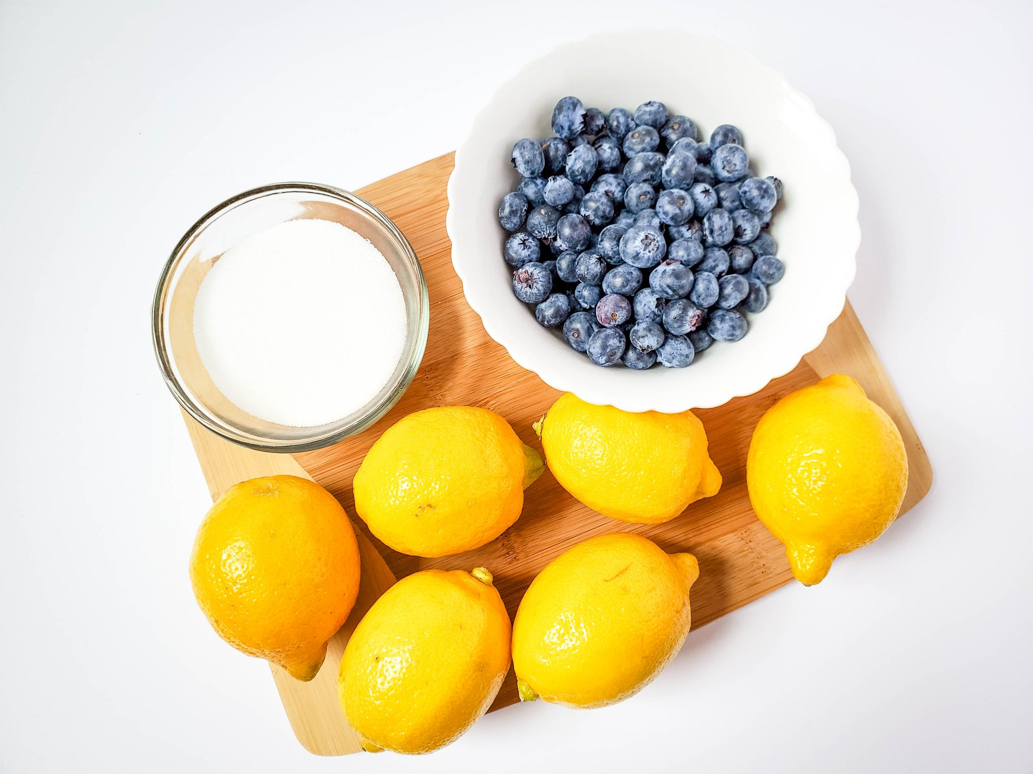 Sugar, blueberries, lemons on a wooden cutting board