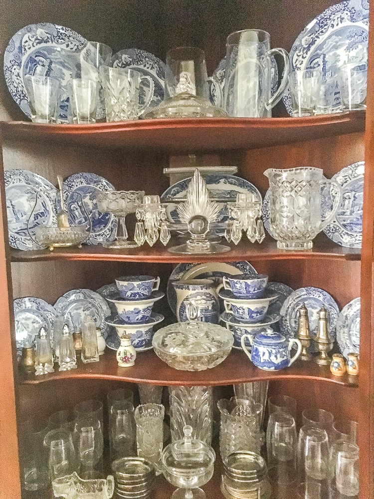 Antique corner cabinet decorated with blue and white china and glassware