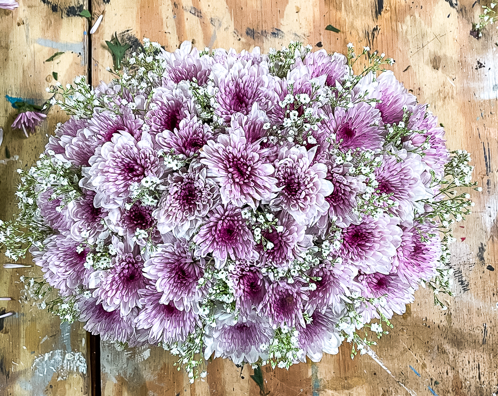 Looking down at a purple Chrysanthemum and Baby's Breath Flower arrangement