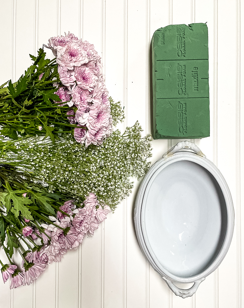 Ironstone container, floral oasis, two bunches of purple chrysanthemum and one bunch of Baby's Breath