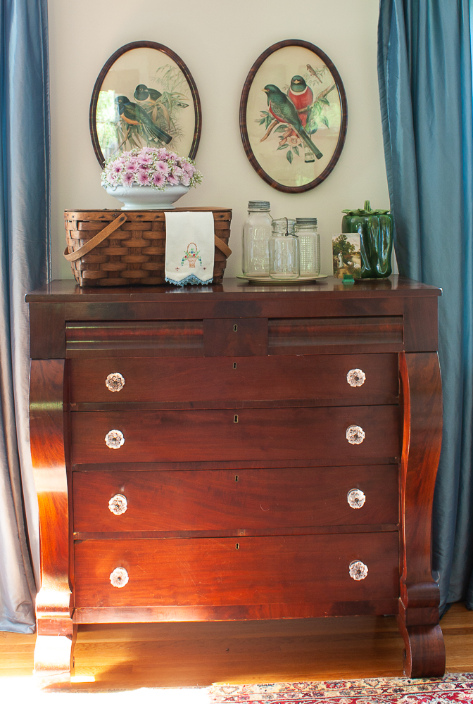 Antique chest of drawers decorated for summer with a picnic basket, flower arrangement, tea towel , Mason jars, a McCoy green pepper cookie jar, and an antique postcard.