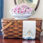 Vintage picnic basket with a floral arrangement, and vintage embroidered tea towel