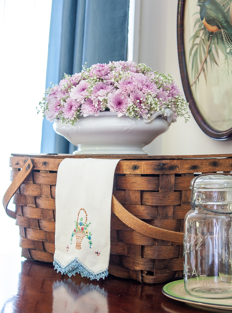 Vintage picnic basket with a floral arrangement in an antique Ironstone serving dish, vintage embroidered tea towel, and a Mason jar
