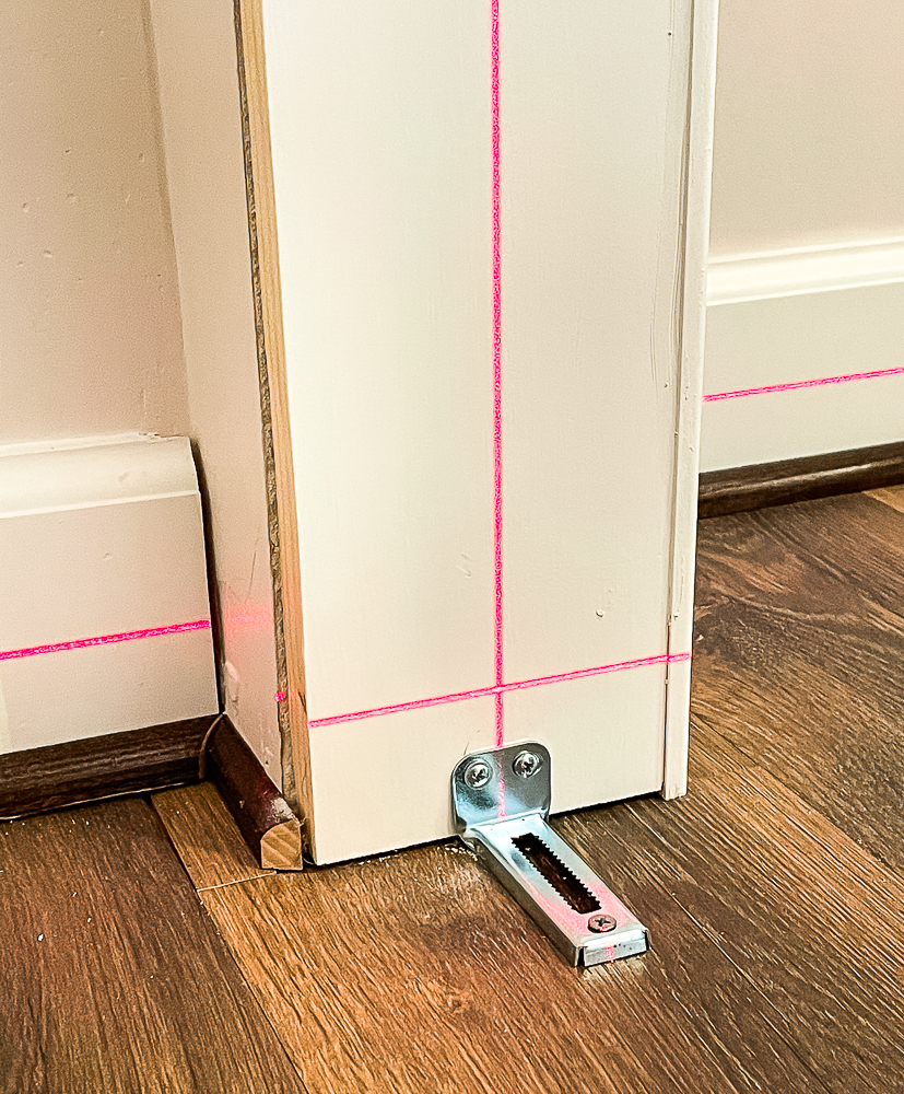 Using a laser level to position floor brackets for bifold closet doors