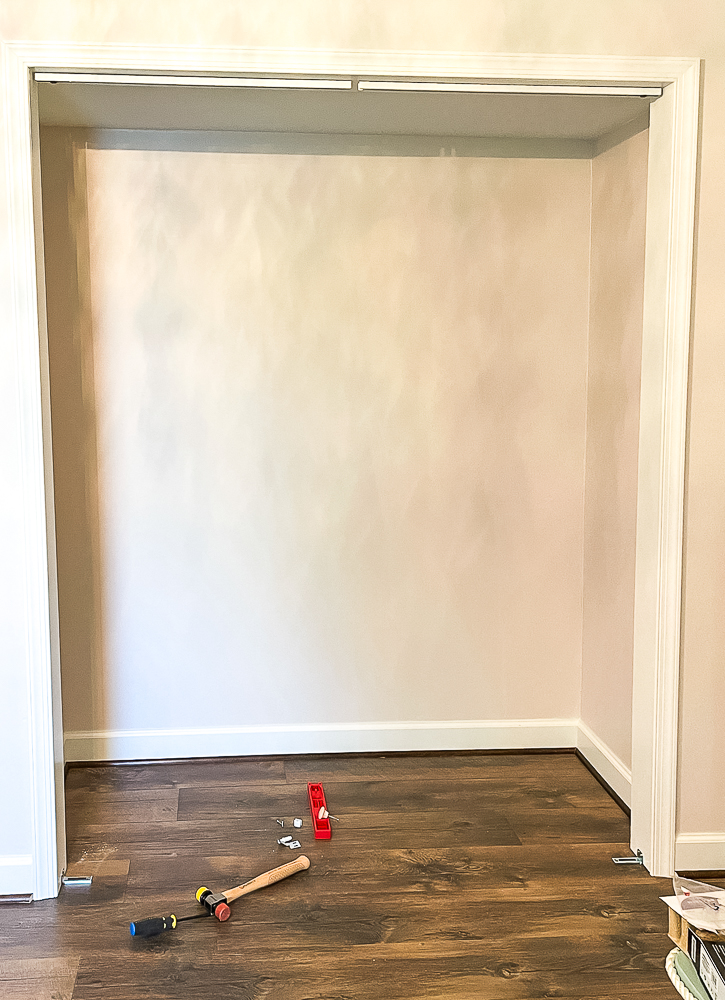 Closet with track and floor brackets installed