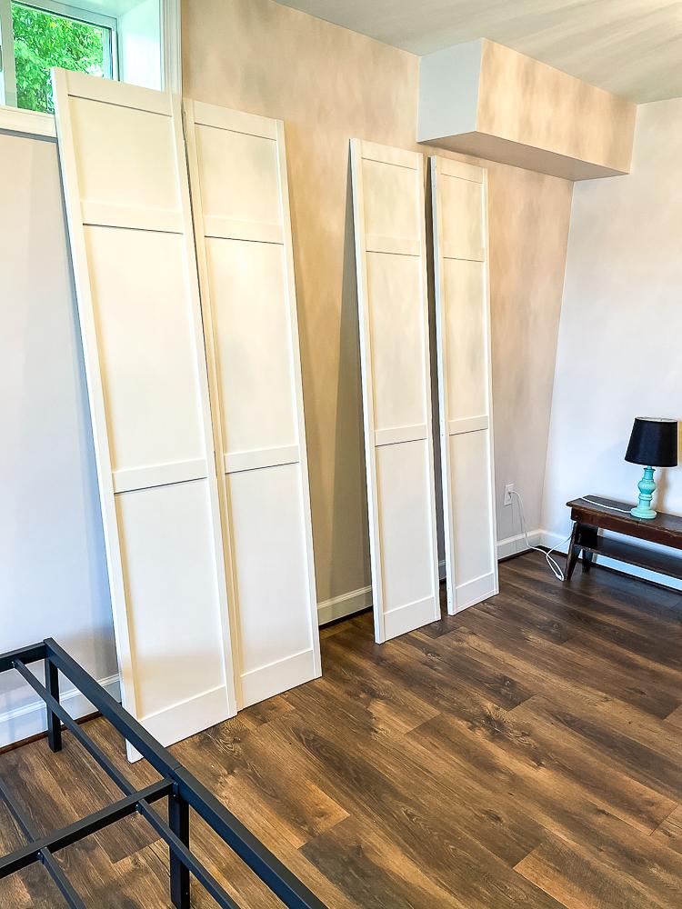 Four painted white bifold closet doors