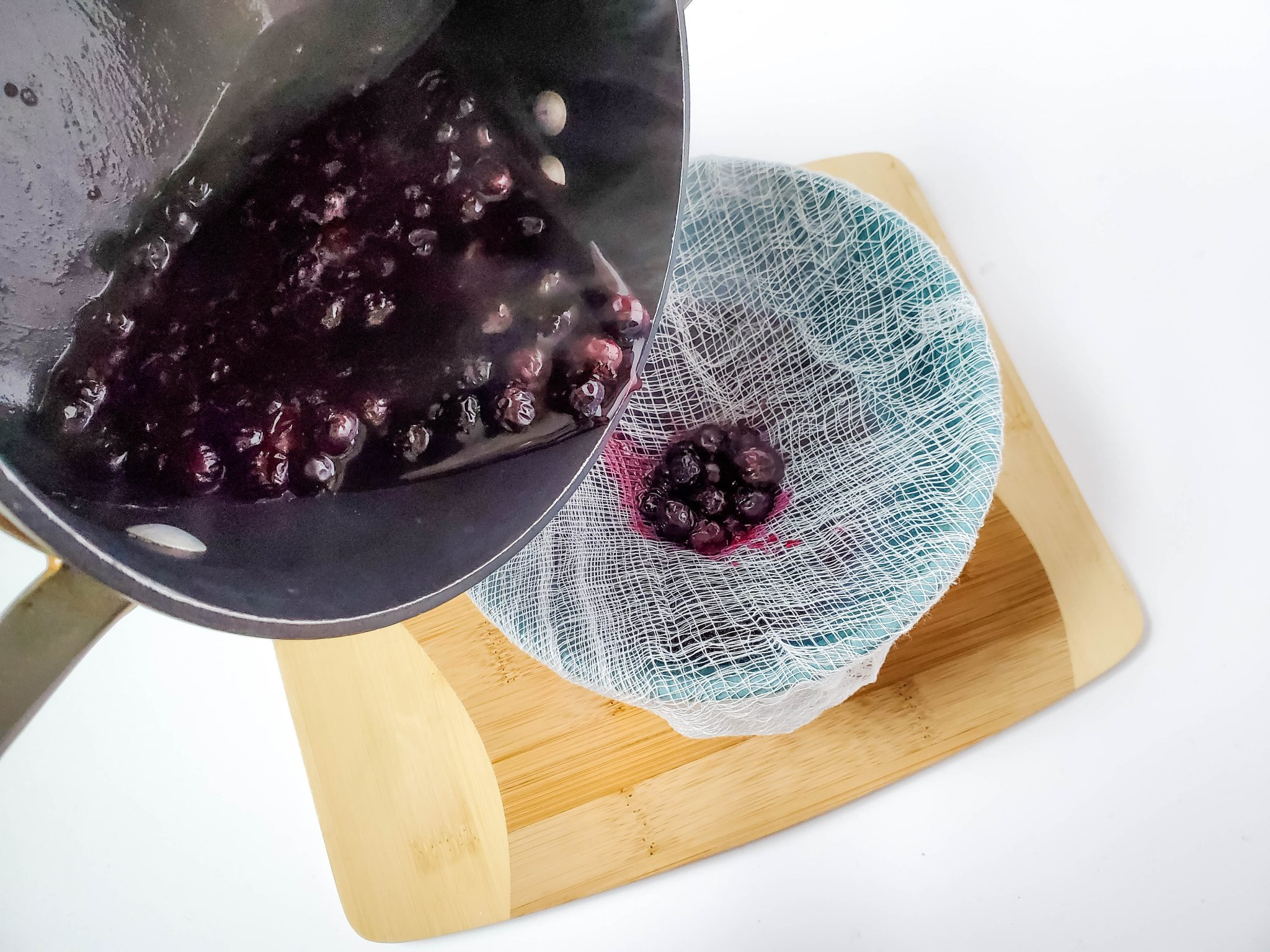 Straining blueberry juice over a bowl lined with cheesecloth
