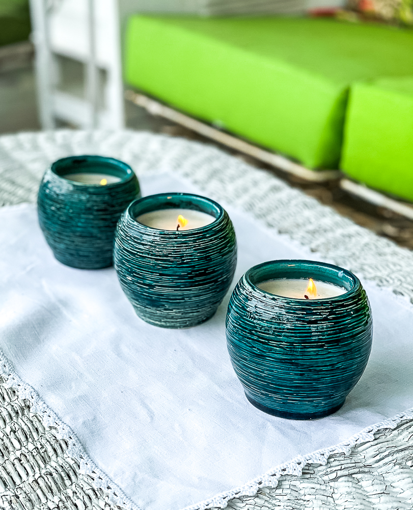 Three homemade Citronella candles on a wicker coffee table on a porch