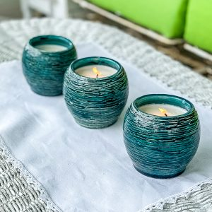 Three homemade Citronella candles on a wicker coffee table