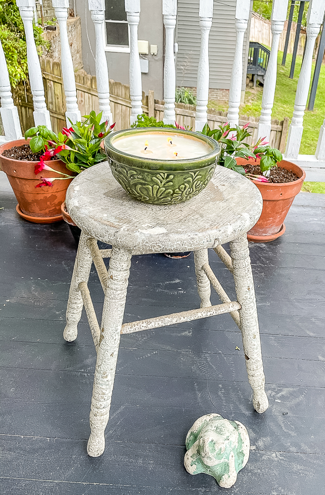 Homemade Citronella candle on an antique stool with potted flowers in the background