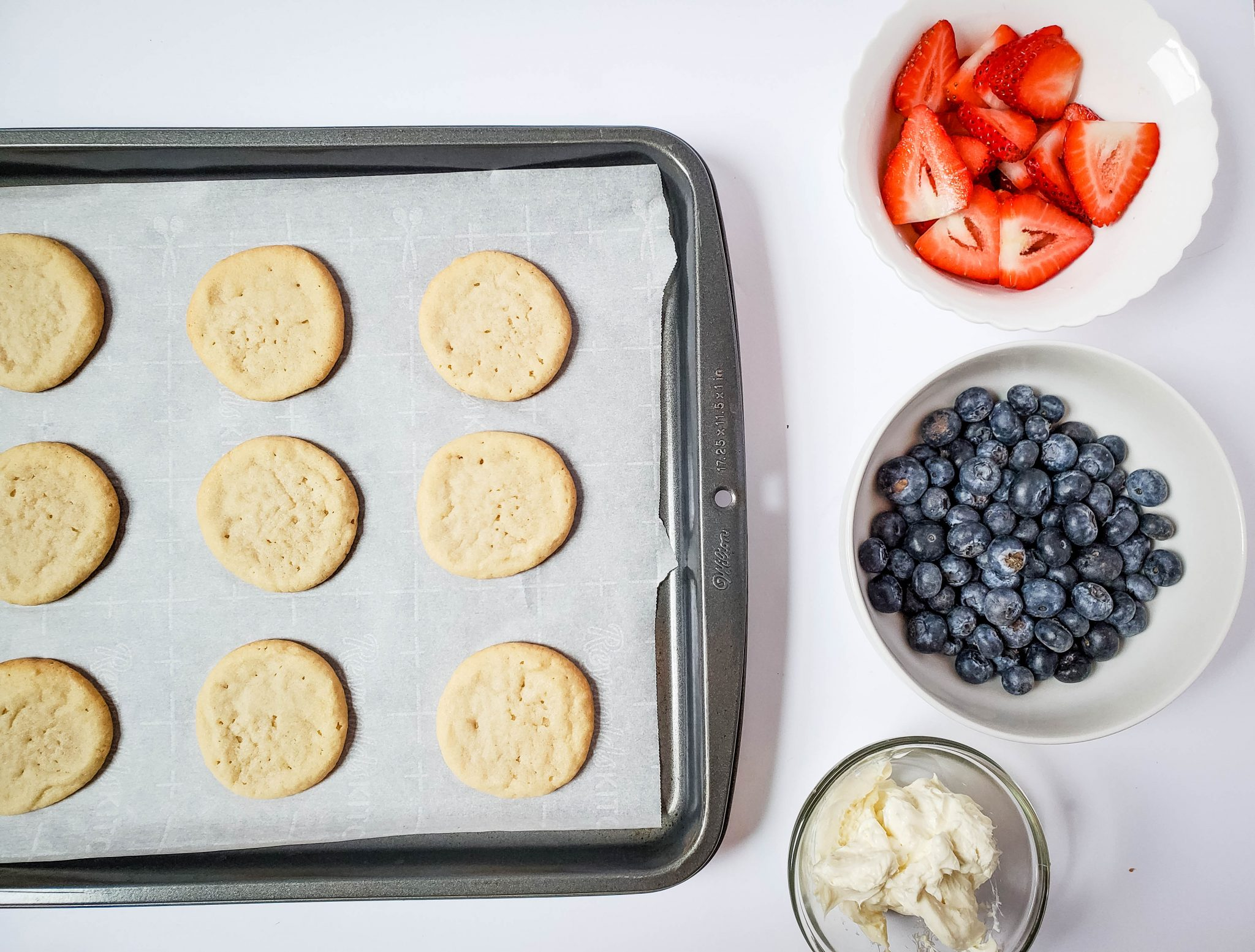 Sugar cookies on a parchment covered baking sheet, white bowl filled with strawberry slice, white bowl filled with blueberry slices, clear bowl filled with cream cheese frosting