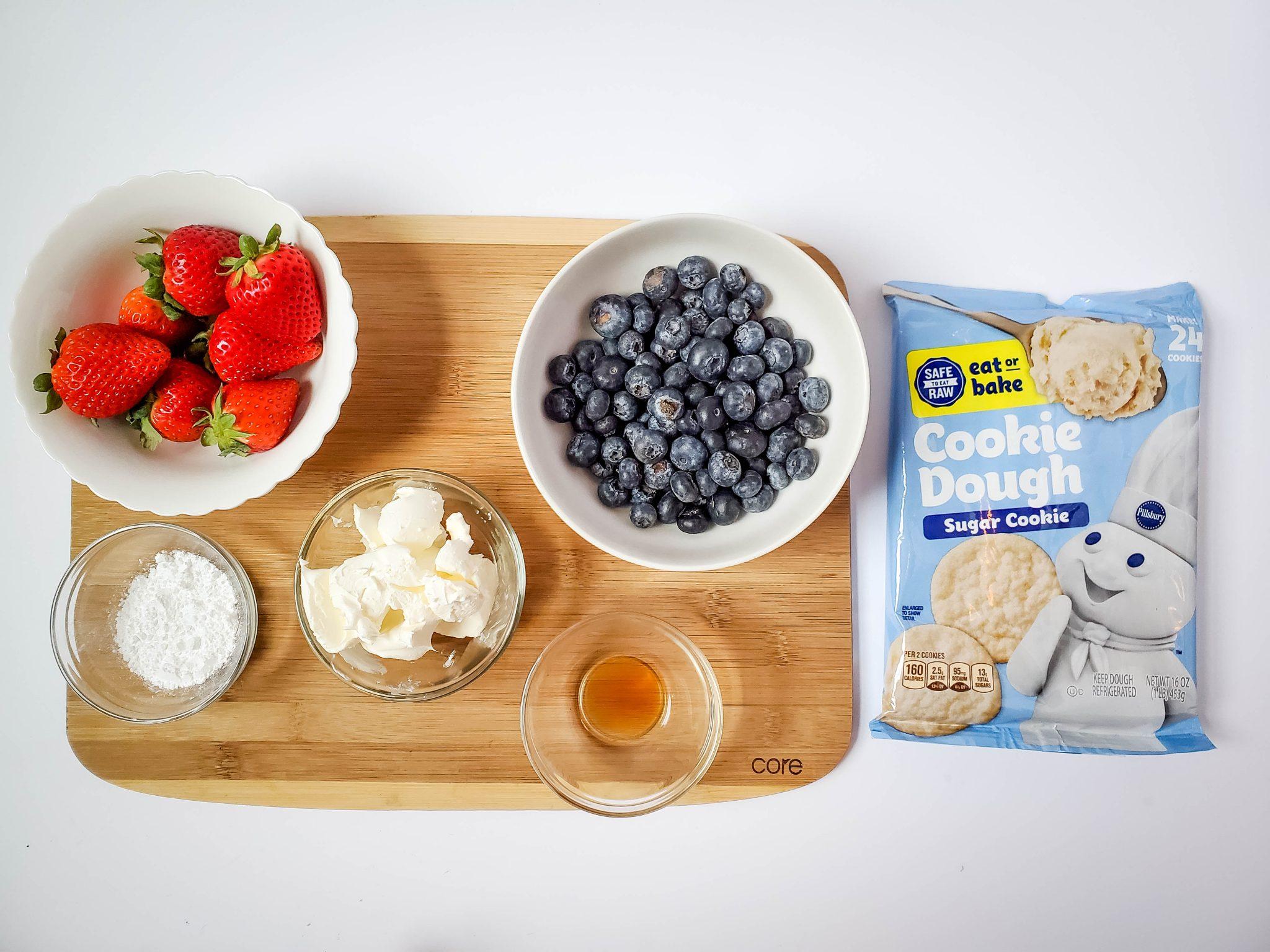 Pillsbury sugar cookie packaged dough, blueberries in a white bowl, strawberries in a white bowl, and clear glass bowls of powdered sugar, cream cheese, and vanilla