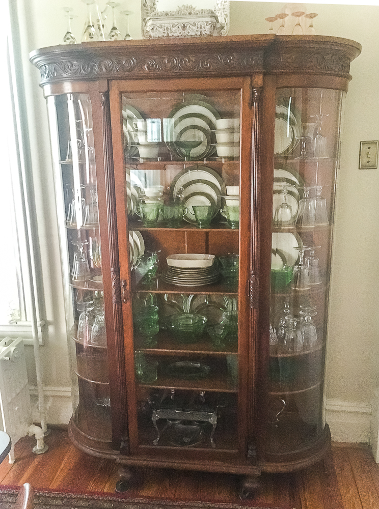 Antique oak china cabinet filled with green depression glass, 1968 china and crystal, and silver