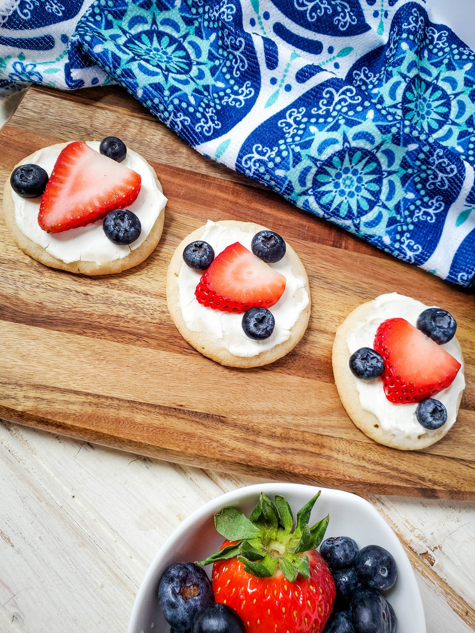 Sugar cookies decorated with a strawberry slice an three blueberries on a wood tray with a blue and white patterned tea towel in the background