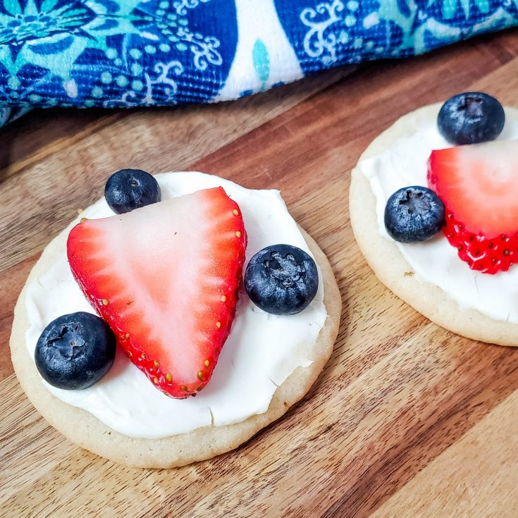Sugar cookie with cream cheese frosting decorated with a strawberry and three blueberries