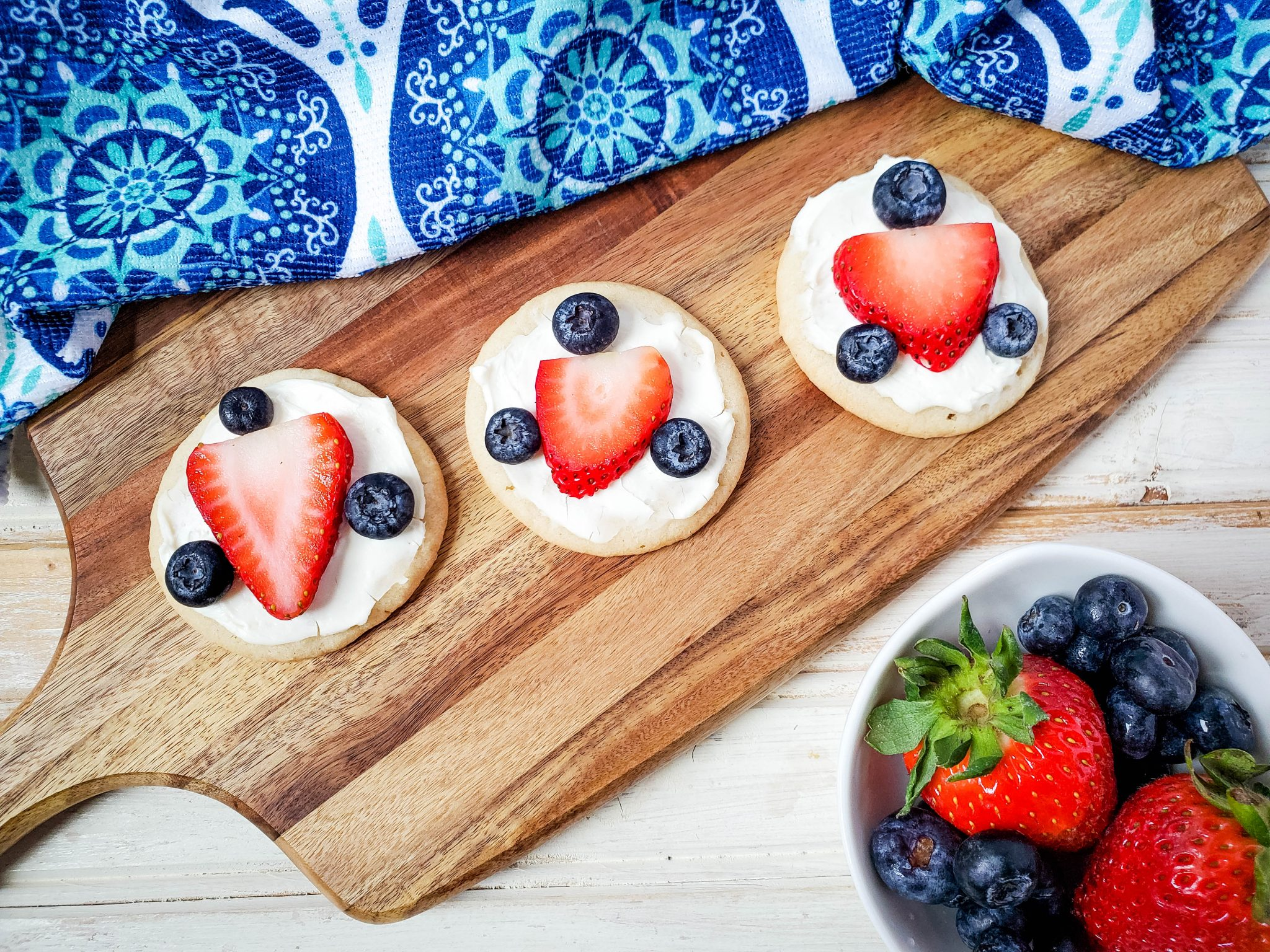 Three sugar cookies with white icing decorated with a strawberry slice and three blueberries on a wooden cutting board