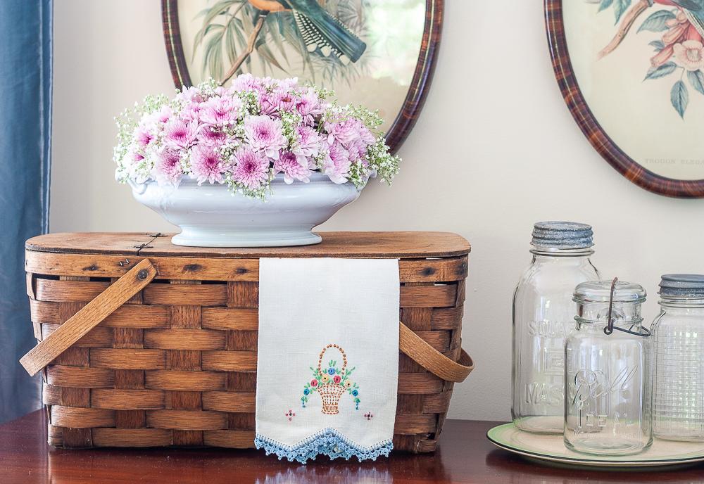 Vintage picnic basket with a floral arrangement, vintage tea towel, and three vintage canning jars on a depression era round cake plate