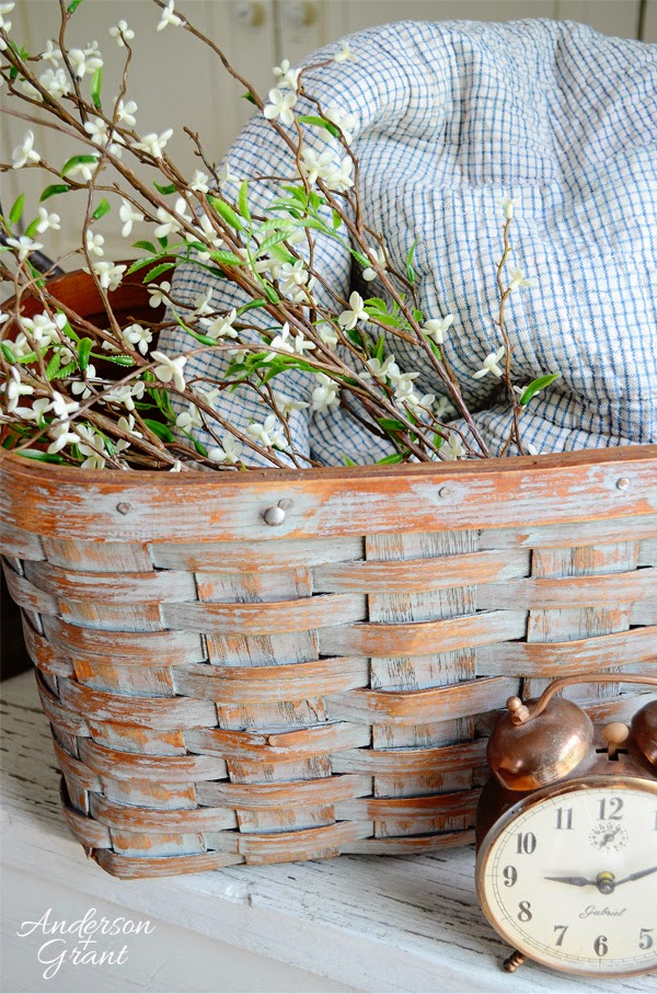 Picnic basket with floral branches, plaid fabric and a clock