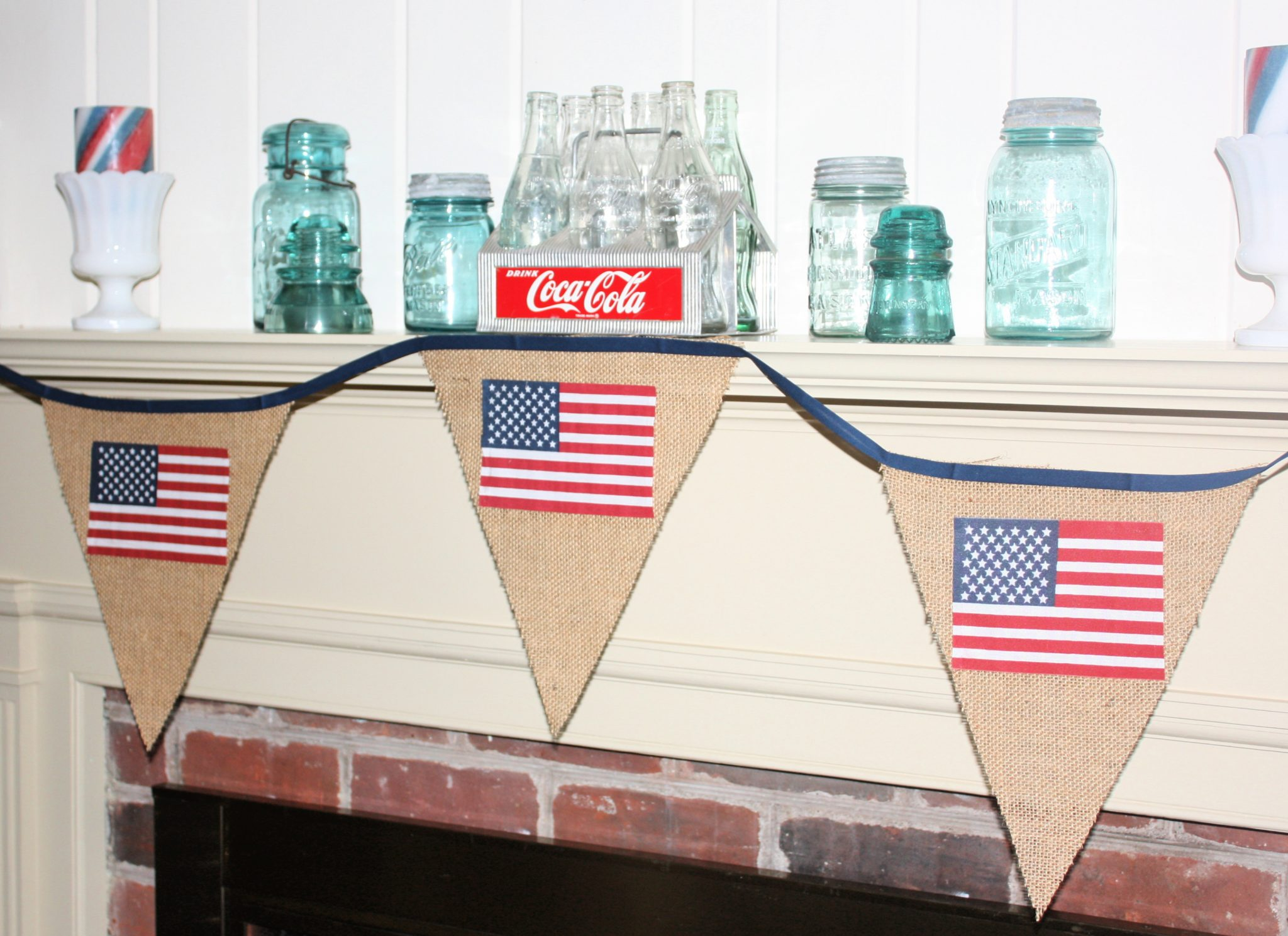Mantel decorated for 4th of July with banner, Coke crate and bottles, vintage Mason jars