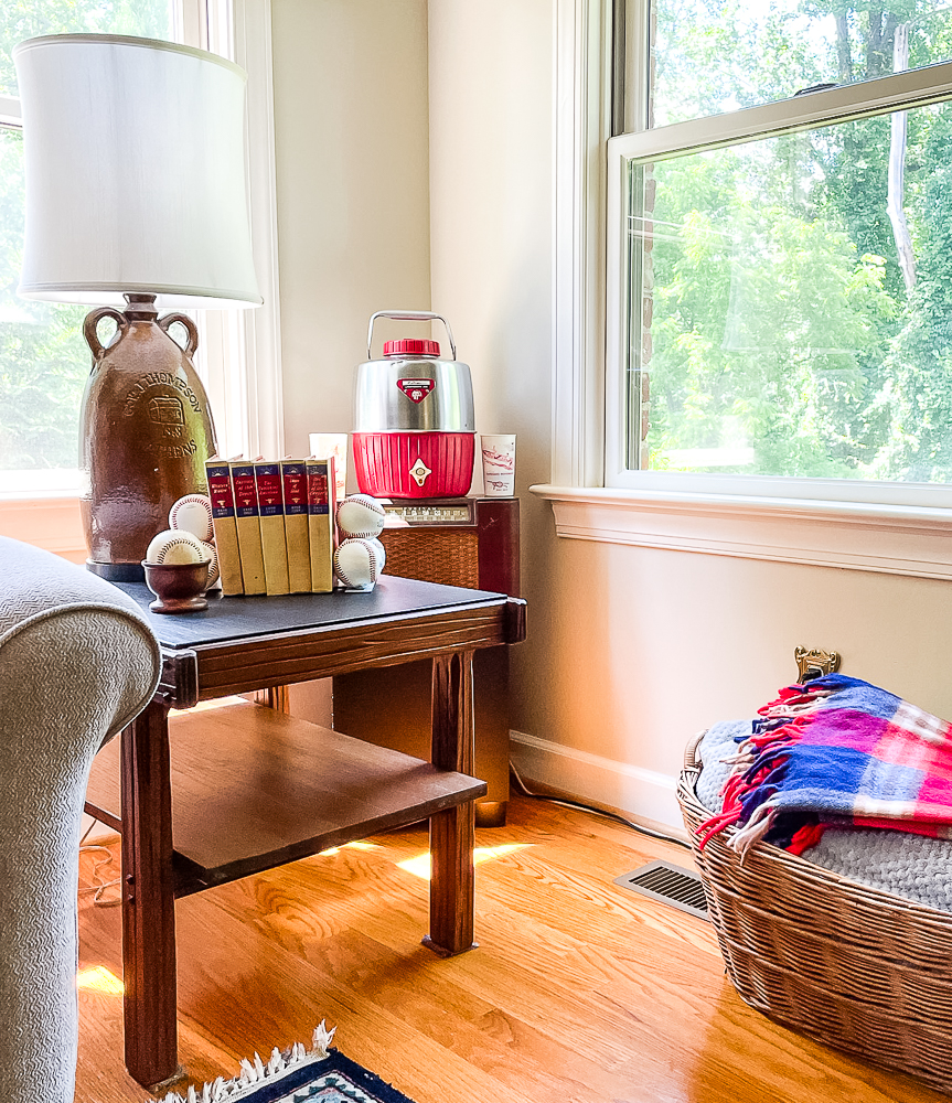 Living room corner decorated with a vintage thermos, baseballs, and Zane Gray books