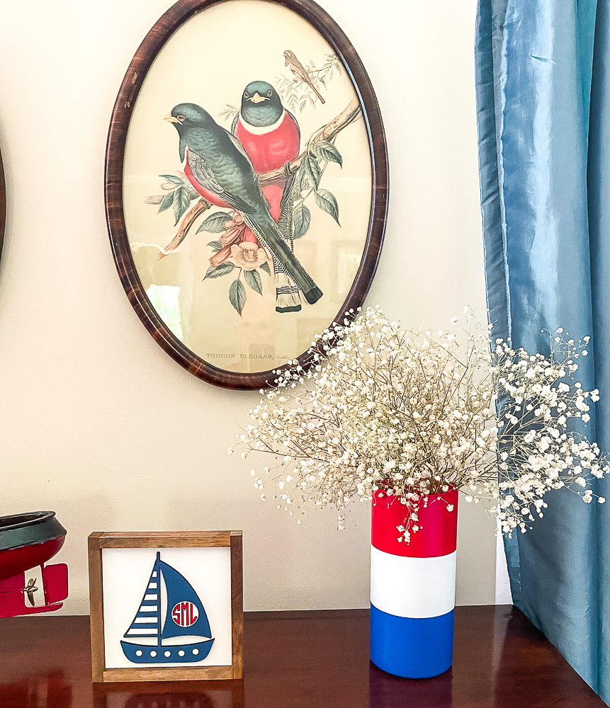 Framed sailboat and red, white and blue vase with Baby's Breath