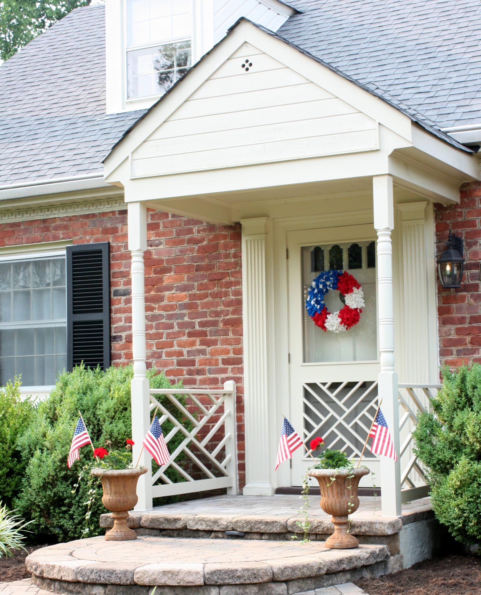 Front porch decorated with a red, white, and blue wreath and flags in flower pots.