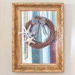 Antique mirror with a gold frame with a wreath decorated in a coastal style