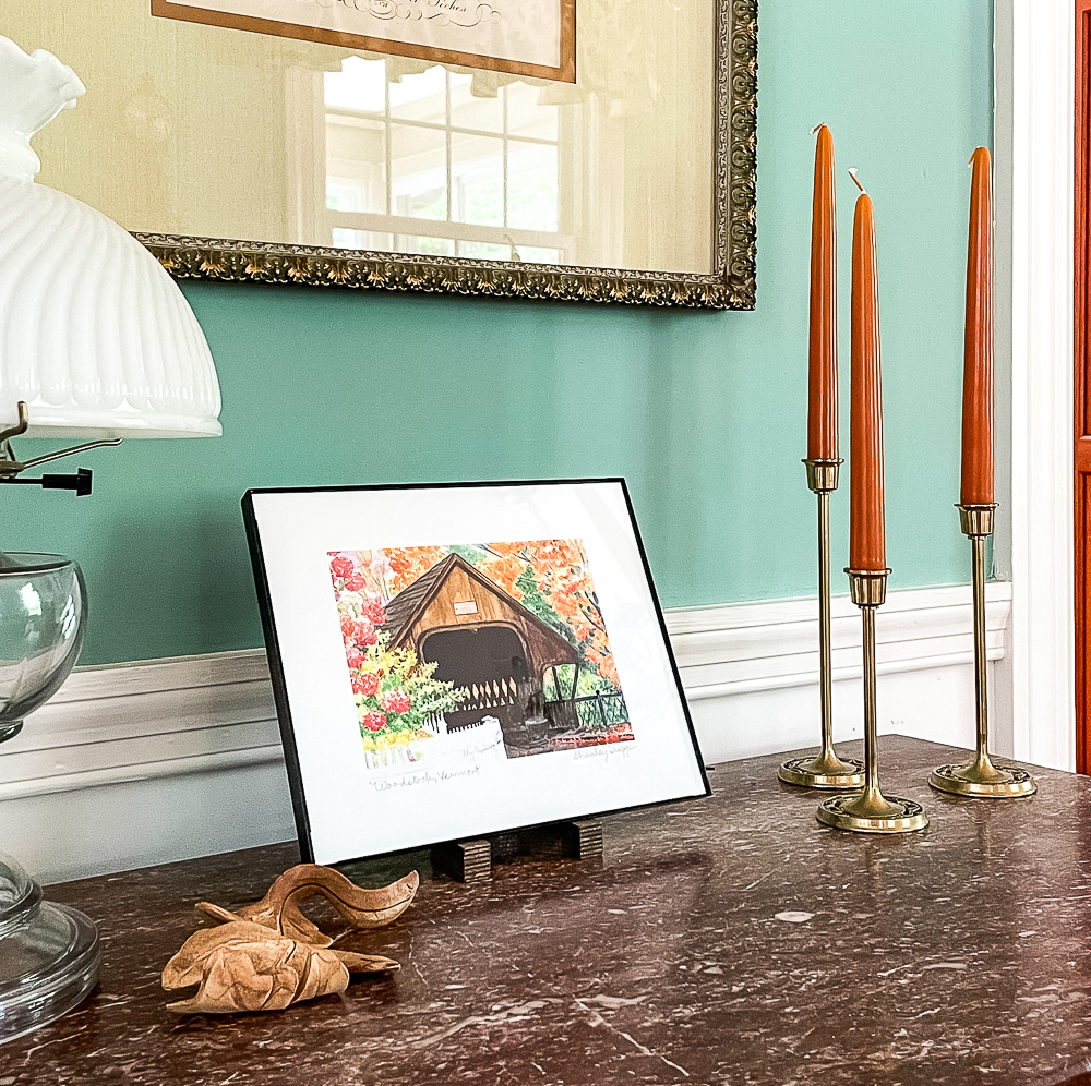 Painting of Middle Bridge in Woodstock, VT with a pottery leaf and three brass candle holders with orange candles