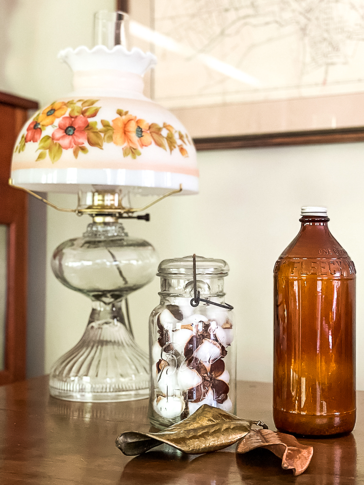 Antique oil lamp, vintage Mason jar filled with cotton bolls, Fleecy White amber bottle, and two preserved Magnolia leaves
