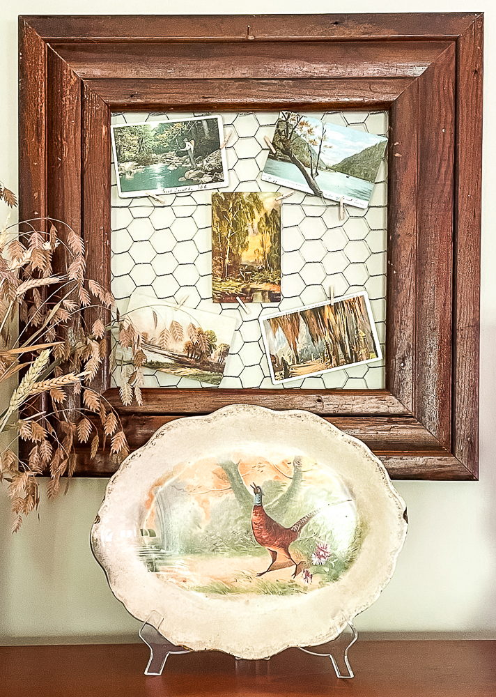 Vintage postcards displayed on chicken wire and a fall pheasant platter