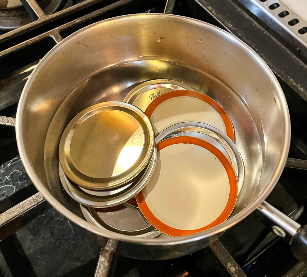canning lids warming in a saucepan