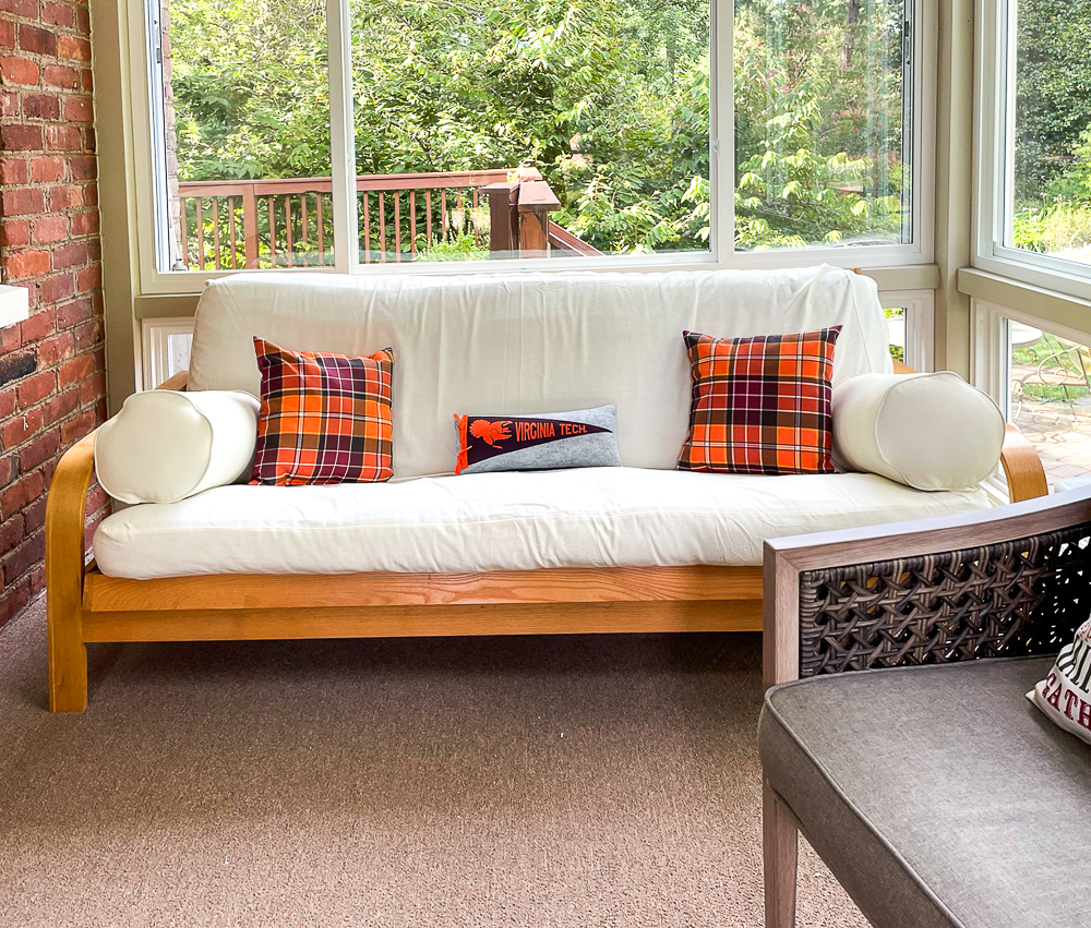 Futon in a sunroom with fall plaid pillows