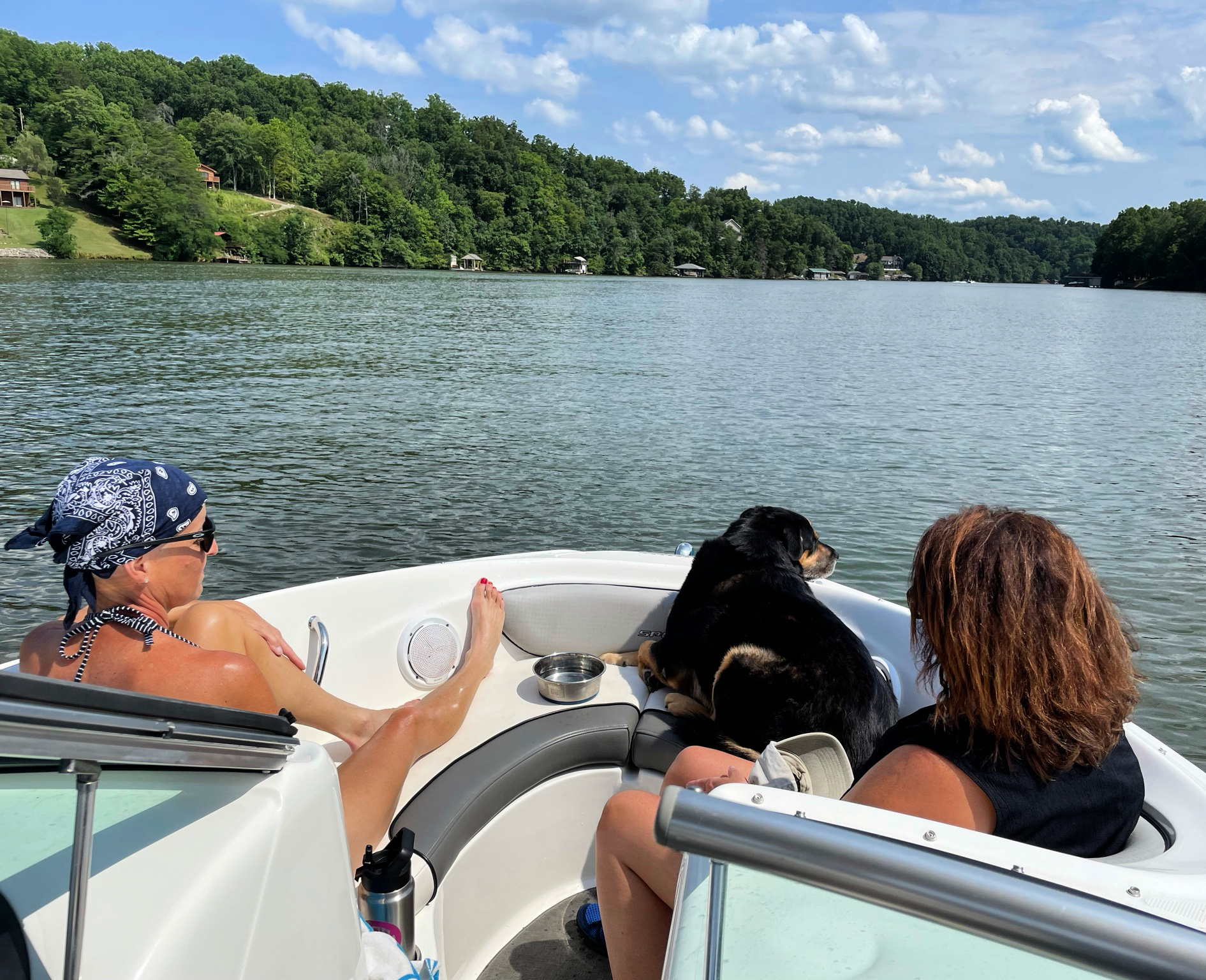 Two women and a dog on a boat at Smith Mountain Lake, VA