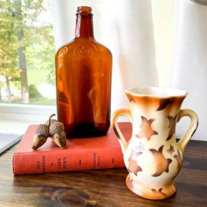 Fall vignette with a Czech vase, amber bottle, acorns and an orange book