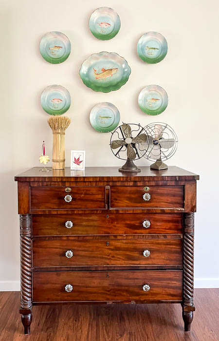 Antique fish platter hanging over a dresser decorate with vintage fans and a fall vignette