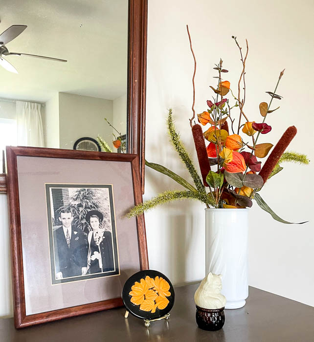 Fall floral arrangement, 1930s wedding picture and belt buckle, Avon cat with basket